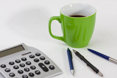 Cup, pens and a calculator. Close-up of a desk with a cup, pens and a calculator Royalty Free Stock Images
