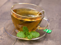 A cup of peppermint tea. With peppermint leaf Royalty Free Stock Image