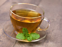 A cup of peppermint tea. With peppermint leaf Royalty Free Stock Images