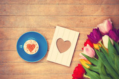 Cup and photo frame near flowers Royalty Free Stock Image