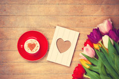 Cup and photo frame near flowers Royalty Free Stock Images