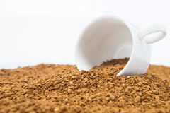 Cup on Pile of instant coffee grains on white background Royalty Free Stock Image