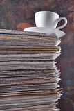 Cup on a pile of papers Stock Photos