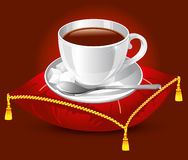 Cup on the pillow. Coffee cup on the red satin pillow with gold tassels Royalty Free Stock Photos