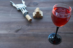 Cup of pink wine on table with corkscrew aside Royalty Free Stock Photos