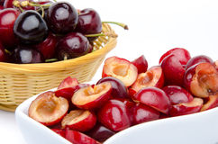 Cup of pitted cherries and whole cherries in a basket Royalty Free Stock Image