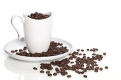 Cup, plate and coffee in grains Royalty Free Stock Photos
