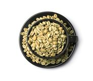 Cup and plate with green coffee beans stock images