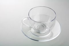 Cup on plate isolated on gray Royalty Free Stock Images