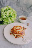 A cup and a plate of pancakes, hydrangea Stock Photo