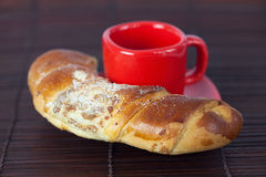 Cup with a plate and roll on a bamboo mat Royalty Free Stock Photography