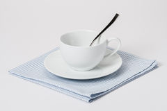 Cup, Plate And Spoon On Folded Gingham Cotton Stock Images