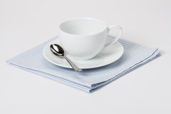 Cup, Plate And Spoon On Folded Gingham Cotton Royalty Free Stock Photos