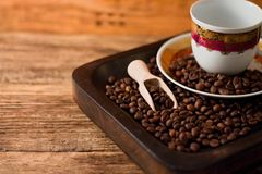 Cup with plate on tray full of coffee beans Stock Photo