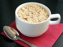 A cup of porridge. A cup of oatmeal porridge for the breakfast Royalty Free Stock Photo