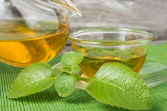 Cup and pot with green tea and mint leaves Royalty Free Stock Images