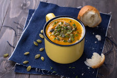 Cup of pumpkin soup with pumpkin seeds, olive oil and thyme Royalty Free Stock Images