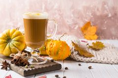 Cup of pumpkin spice latte with whipped cream on top and seasonal autumn spices, and fall decor. Traditional coffee drink. For autumn or winter holidays, copy stock photography