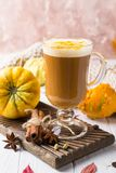Cup of pumpkin spice latte with whipped cream on top and seasonal autumn spices, and fall decor. Traditional coffee drink. For autumn or winter holidays, copy royalty free stock photography