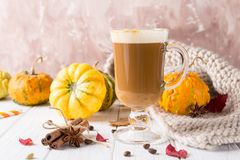 Cup of pumpkin spice latte with whipped cream on top and seasonal autumn spices, and fall decor. Traditional coffee drink. For autumn or winter holidays, copy royalty free stock photos