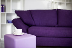Cup and purple couch Stock Photography