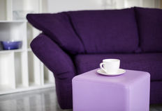 Cup and purple couch Royalty Free Stock Photography