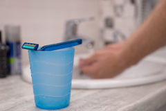 Cup with a razer on it and man washing his hahds on a background Stock Image