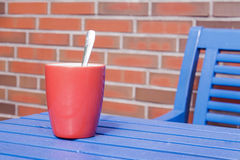 Cup. Red cup on a blue wooden table Royalty Free Stock Image
