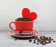 Cup red with coffee grains, heart and an inscription bon appetite. Cup red with coffee grains, heart  and an inscription bon appetite  on a table Royalty Free Stock Image