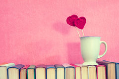 Cup with red crochet hearts on books. Valentines day concept. Cup with crochet hearts on books over pink background Stock Images
