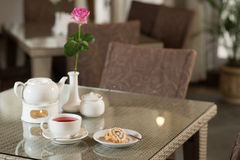 Cup of red tea, cake and rose on a table Stock Photos