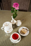 Cup of red tea, cake and rose on a table Stock Photography
