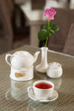 Cup of red tea, cake and rose on a table Royalty Free Stock Images