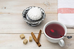 Cup of red tea. Cane sugar and cinnamon sticks with sweet dessert Stock Images