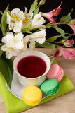 Cup with red tea and colored cakes Stock Images