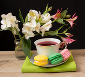 Cup with red tea and colored cakes Royalty Free Stock Photos