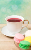 Cup of red tea and colored cakes Royalty Free Stock Image
