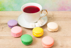Cup of red tea and colored cakes Royalty Free Stock Images