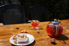 Cup of red tea and cookies on a table. Berry tea in a kettle on a blurred outside background. Cafe breakfast concept. Royalty Free Stock Images