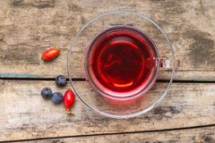 Cup of red tea with wild berries on wood background Royalty Free Stock Photo
