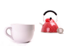 Cup and red teapot. Cup in the foreground with a red teapot in the background. Isolated on white Royalty Free Stock Photos