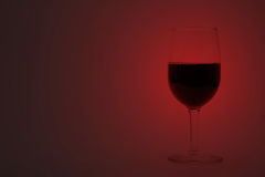 Cup of Red wine. On red background light Stock Photos