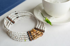 Cup of refined sugar and a necklace on white- blue background Stock Photography