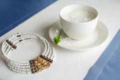 Cup of refined sugar and a necklace on white- blue background Royalty Free Stock Photos