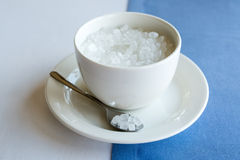 Cup of refined sugar on the white- blue background Stock Images