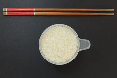A cup of rice with a pair of chopsticks stock photography