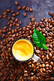 Cup of rich frothy coffee with coffee beans Royalty Free Stock Photo