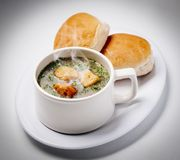 Hot soup cup and bread. Cup of rich and warming soup with clutches royalty free stock photos