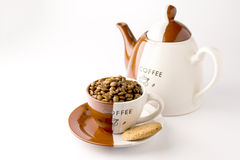Cup of roasted brown coffee beans. On white background in coffee cup wilt coffee pot stock photography