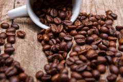 Cup with roasted coffee beans. Royalty Free Stock Image